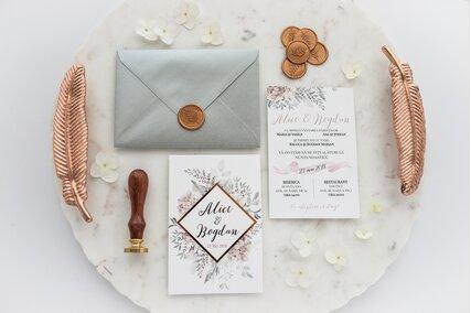 invitatie eleganta cu flori si verdeata cu text rose gold si banda geometrica aurie cu sigiliu